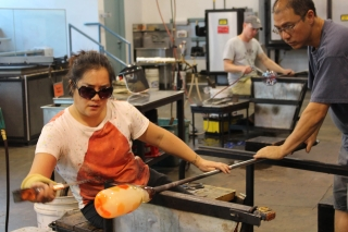Students work with hot glass at a class in The Studio