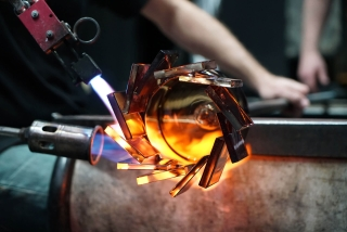 A close up of a gaffer creating an amber glass cup with square pieces of glass around the lip of the cup