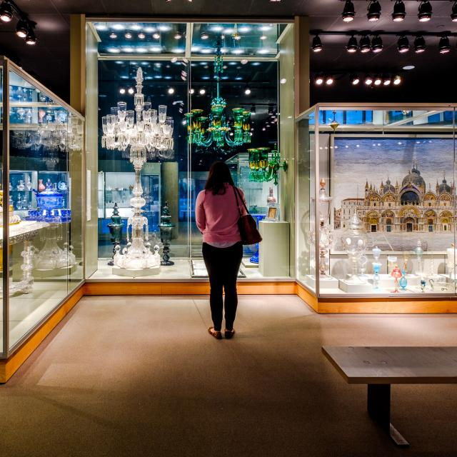 A guest stands in the middle of a gallery of glass objects in exhibit cases