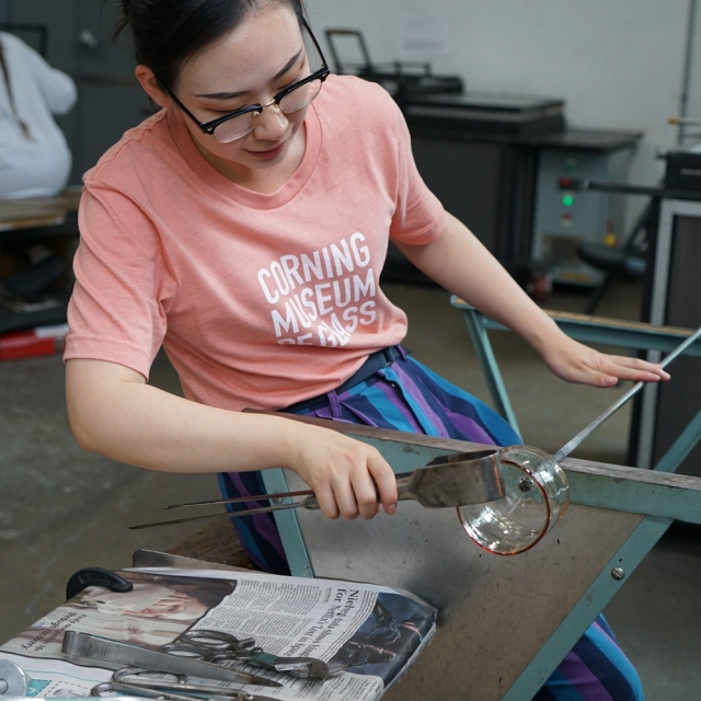 A gaffer uses the flat part of a jack to smooth the lip of a cup-shaped piece of clear molten glass