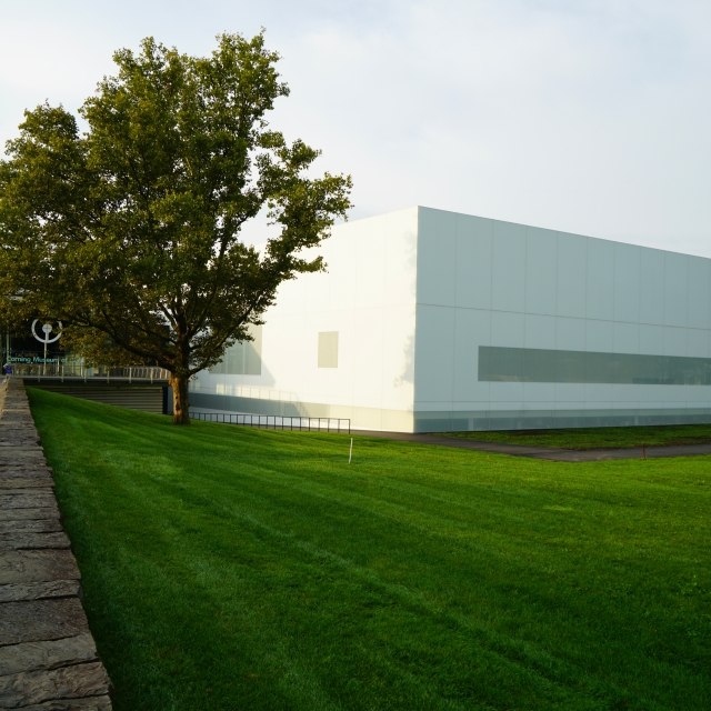 A white rectangular building is surrounded by a green lawn and green trees.