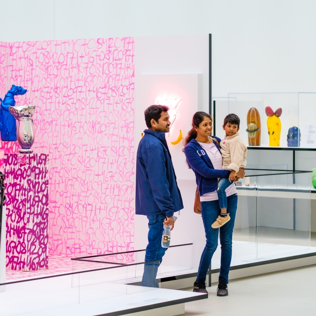 A family of three stands in front of a bright pink installation in the Contemporary Art and Design Wing